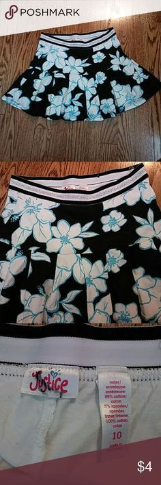 Hawaiian flower print girls 10 skirt Cute great worn condition. Black with white and aqua flowers throughout. Shorts underneath. Stretchy waist line with silver shimmering line. Justice Bottoms Skirts