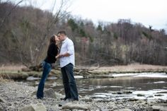 A couple kissing on the rocks by a river. Copyright Photographics Solution 2013