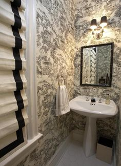 A tiny half bath done in a Blake and white toile with Roman shades