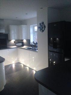 More of our wren kitchen. White gloss handless, grey slate work top and flooring. Black fridge freezer, breakfast bar, tech wall