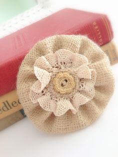 Super cute Burlap and Lace flower.. This would be pretty easy to make.. Looks like the burlap piece is a Yo-Yo, then gather a piece of lace, and add a button..