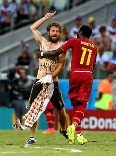 Sulley Muntari of Ghana removes a pitch invader with Nazi-inspired messages on his chest