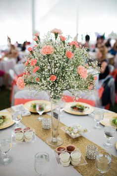 Coral + white wedding centerpiece idea - coral carnations with white baby's breath in tall clear glass vase displayed on gold sequin table runner {Rockhill Studio}