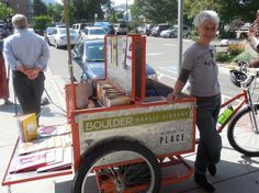 """On a sunny September day in Boulder, Colo., a group of librarians from the Boulder Public Library parked a bright orange, book-filled tricycle in front of Alfalfa's Market and lofted a sturdy sun umbrella over it to shade the curious who approached to investigate. They offered free books and temporary tattoos (""""I ♥ the Boulder …"""