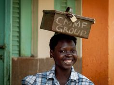 A woman smiles as she transports a box on her head.