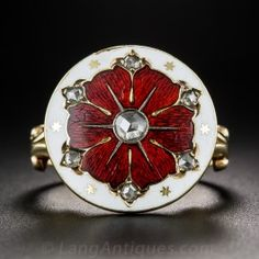 Measuring 11/16 inch round, this beautiful uniquity is colorfully adorned with rich red guilloche enamel encircled by white enamel and dotted with seven glinting rose-cut diamonds and tiny gold stars, all supported by fanciful split 'V' shoulders. Crafted in 14K rosy-yellow gold, we're never seen a ring quite like this but we have a hunch it might be of Russian origin. Circa 1890-1900. Currently ring size 5.