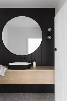 Dark joinery and pops of terrazzo steal the show in this modern home makeover. Black panel wall in powder room, cool powder room with round mirror, black sink in bathroom