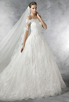 Brides: Pronovias. Off-the-shoulder princess-style dress.  Elbow-length, sheer sleeves with lace appliqués. Sheer back with appliqués. Tulle and lace skirt with gathers at the waist.