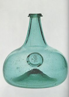 The delicate pale green glass of this early 18th century wine bottle is extremely unusual I Bottles of the period were almost always made in the usual dark green or greenish-brown metal that one thinks of as bottle glass, and any variation is rare I Moreover, the seal is named and dated: Roger Comberbach I 1725