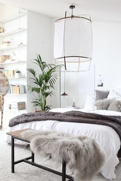 Swedish bedroom with a reclaimed wood bench at the foot of the bed, and a paper lantern above