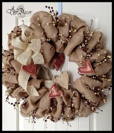A large natural colored burlap with ivory & rustic red berries wreath would look great on your wall or front door.  Wood hearts are painted a rustic red