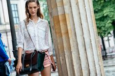 Stunning in a eyelet blouse and carrying a Celine trapeze bag. Berlin #Offduty