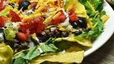 Seasoned ground beef and black beans form the basis of a hearty taco salad with layers of lettuce, salsa, Mexican cheese blend, and sour cream and topped with tortilla chips.