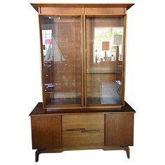 A gorgeous teak and glass cabinet from the Mid-Century. It features etched…