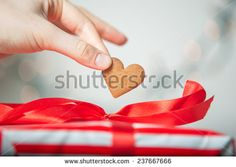 Girl Fingers Holding Hearth Shaped Gingerbread Cookie, blurred background, vintage edition - stock photo