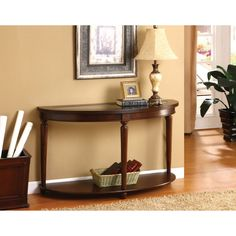 This beautiful console table features a crescent shape and a rich, dark cherry finish. Solid ball feet stabilize this handsome entry way table.