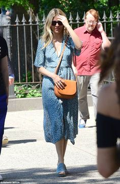 Floral finesse:The blonde beauty looked typically stylish in a plunging powder blue floral dress with a flowing skirt which flashed a hint of her toned legs