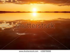 Stock Photo: Idyllic sunset with some clouds in summer. Dramatic reflection of the Sun in the still water of a lake in Finland.