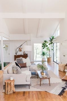 A boho-styled Tulsa Home, layered rugs, neutrals, white walls, wood stump table, coffee table, tree