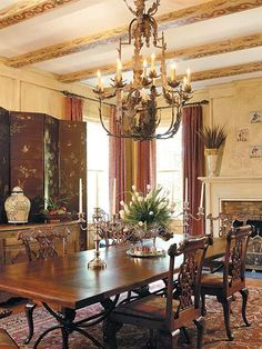 This formal dining room makes entertaining easy. The decor of the room is accented by exposed ceiling beams, from which hangs the rusted antique chandelier.