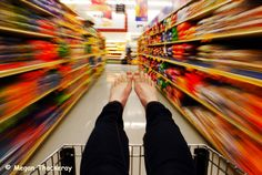 Paleo AIP Grocery List: photo of feet in a shopping cart being pushed down a grocery aisle at high speed