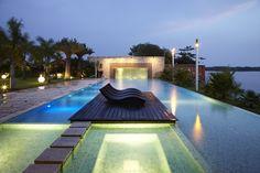 Esta piscina luxuosa conta com uma cascata (ao fundo), um deck com espreguiçadeiras e vista para a paisagem natural da cidade de Assinie-Mafia, na Costa do Marfim. Projetada pelo escritório Koffi