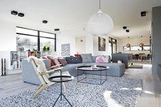 aménager le salon contemporain avec un canapé gris clair, un tapis ne blanc et gris, deux tables basses noires et une chaise en bois clair