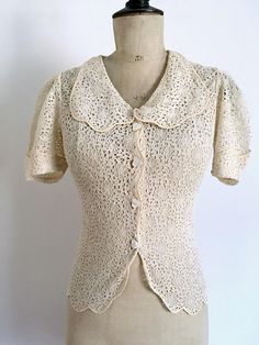 • Adorable vintage beige lace blouse from the late 30s or early 40s. Small short sleeves cuffed balloons. Nice wide neck. Closes in front by 4 small pearl buttons art deco and a small pressure. Shoulders and sleeves Belt loops at the waist.  • Brand: No brand, entirely handmade by a