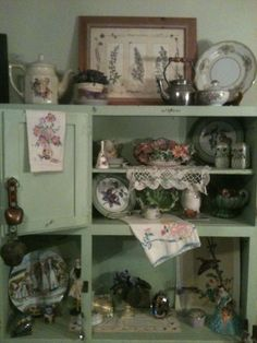 Sandra uses her old Hoosier Cabinet to display her many heirlooms.  This is an idea for those of you who may come across a Hoosier with some of the doors off or interior components removed.  It shows how they still can be beautiful and useful.  It's nice to see the combination of vintage linens, a print, the pressed flowers in the frame on the top shelf, the cow bells, and all kinds of odds-and-ends that you know have family meaning.