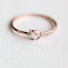 The Flurry ring is delicate and dainty, and features a scattering of sparkling white diamonds over a slim round band. This asymmetrical ring design featues a 4mm rose cut white diamond focal stone, and small sparkling white diamond accents. Diamonds: • 4mm rose cut white diamond • 1.5mm & 1mm accent white diamonds (I2 clarity, G-H color)  ♦ Metal: Solid 14k gold ♦ Setting: Prong setting ♦ Ring Band: Smooth, delicate band, 1.1mm wide   ♦ Item number: R1044 ♦ This listing is for one ring ♦ ...