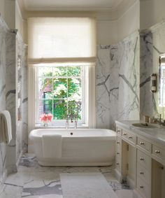 Frog Hill Designs blog White carrara marble walls and floor surrounds this white pedestal tub.  Love that it is placed under the window.  #whitebathroom #pedestaltub