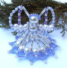 Vánoční andílek modro-fialkový Andílek je vyrobený ze skleněných korálků, tyčinek a rokailu, v bílé, stříbrné a modro-fialkové barvě, doplněno fialkovými sluníčky. Výška 4,5 cm s křídly. Je vhodný na postavení i pověšení či jako drobný dárek pro Vaše přátele.
