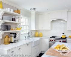 The open shelving in the kitchen creates interest and is used for daily dishes, making it easy for homeowners.  The white ceramic tile backsplash looks beautiful in the white kitchen.