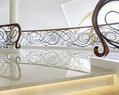 www.trabczynski.com ST490 Dwustronne policzkowe schody gięte montowane na wylewce betonowej. Policzki z malowanego dębu, balustrada z ręcznie kutej stali z drewnianym pochwytem. Stopnice kamienne. Realizacja w prywatnej rezydencji, Projekt – TRĄBCZYŃSKI / ST490 Double-sided curved stringer stair mounted on a concrete substructure. Stringers of painted oak, a hand-wrought steel balustrade with a wooden handrail. Stone treads. Private residential project, designed by TRABCZYNSKI