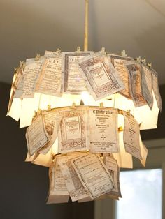 Book Light The pages of a book that are adorned with an elaborate typeface and detailed artwork were used to create a tiered light fixture.  The book pages were fastened to the old chandelier frame using simple binder clips.