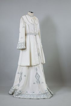 Wedding dress. Athens, Greece 1970 Off-white crepe wedding ensemble embroidered with light blue, silver and grey floral and geometrical designs by C. Mavropoulos, Athens. It consists by a long dress and a folk style sleeveless overcoat. Embroidered by Dinos Mavropoulos.