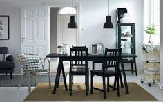 Um espaço de refeições com uma mesa e cadeiras em preto. Em combinação com um carrinho bege e uma vitrina em cinzento escuro.