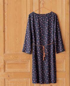 O vestido em crepe suave, estampado flores. Corte direito. Atilho fino em pele a terminar com borlas, para atar na cintura