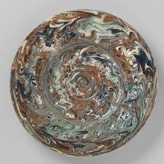 Anonymous | Schotel van loodglazuur aardewerk, met verdiept plat. Versierd met cirkels in reliëf en noppen afgewisseld met kuilen. Veelkleurige sliblagen., Anonymous, c. 1575 - c. 1625 | Schotel van loodglazuur aardewerk. Het plat is verdiept en versierd met drie concentrische cirkels in relief, waar omheen twee cirkelvormig gerangschikte reeksen van kuiltjes. De brede rand heeft een reeks noppen afgewisseld met kuiltjes. De schotel is bedekt met roodbruine, blauwe, groene en paarse en…