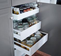 Offene Schranktür mit drei Schubladen, die Glasbehälter für Nahrungsmittel enthalten.