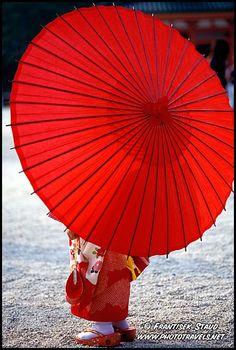 Little Maiko girl posing with red umbrella in Heian Jingu Shrine, Kyoto, Japan.  by Frantisek Staud.  Photo Ref. No: geisha-p-011