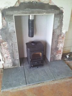 Wood burning stove in a fireplace connected to a chimney liner. Fitting wood burning stove in a fireplace: introduction Wood, Exposed Brick, Stove, Burner Stove, Old Fireplace, Fireplace Surrounds, Wood Burning Stove, Fireplace, Fireplace Hearth