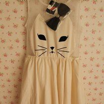 Love cats? You'll love this dress. Featuring an apron-type style with a mesh backing and a detachable bow, this will be the purrfect addition to your wardrobe. One size fits all (S-M).