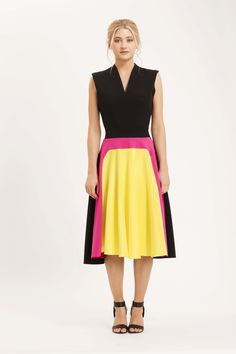 The Venice dress is sleeveless with v-neckline and a very full skirt. Made from black crepe with a block of yellow lined with hot pink on the front skirt panel. Finished with exposed gold zip at the back. Black, yellow and hot pink