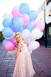 9da1d296b79 Little five-year girl in a pink dress holding balloons