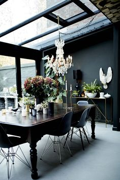 dining space with glass ceiling, chandelier, vintage table paired with Eames chairs