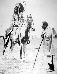 Unidentified Blackfoot Chief On Horseback Speaking To An Elderly Man, 1910.....Two Blood Tribe members, one on horse in ceremonial dress, and the other standing on the ground leaning on walking stick in normal attire.