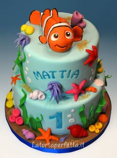 This Superb Finding Nemo 1st Birthday Cake is a 2 tier cake that is blue like the ocean with a 3-D Nemo on top and sea shells, star fish, corals, and anemomes on the side of the cake.