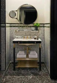 Photo courtesy Viceroy New York design by Roman and Williams Marble top vanity with black and touches of gold, grey marble floor in herringbone pattern.*