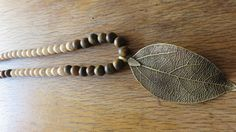 Sautoir pendentif feuille métal perles écru et chocolat : Collier par les-ptits-pois-sont-rouges